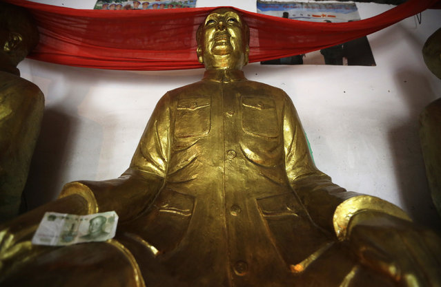 An offering of one yuan is placed on the hand of a gilded statue of China's late Chairman Mao Zedong at a Buddhist temple in a village northeast of Chengdu, Sichuan province, June 8, 2013. The small temple was built around 2005 by local residents as a symbol of their gratitude and affection to Mao and other Chinese communist leaders. (Photo by Jason Lee/Reuters)