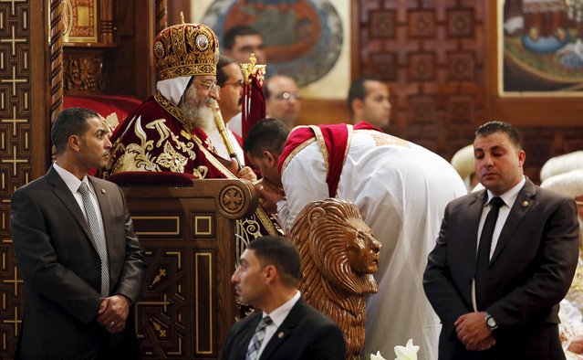 Pope Tawadros II (seated), the 118th Pope of the Coptic Orthodox Church of Alexandria and Patriarch of the See of St. Mark Cathedral, is surrounded by guards as he leads Egypt's Coptic Christmas eve mass, in Cairo, Egypt, January 6, 2016. (Photo by Amr Abdallah Dalsh/Reuters)