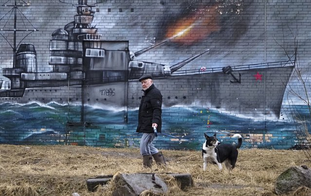 A man walks with his dog past a graffiti on the wall of a building depicting a World War II era Soviet warship in St. Petersburg, Russia, Tuesday, March 30, 2021. (Photo by Dmitri Lovetsky/AP Photo)