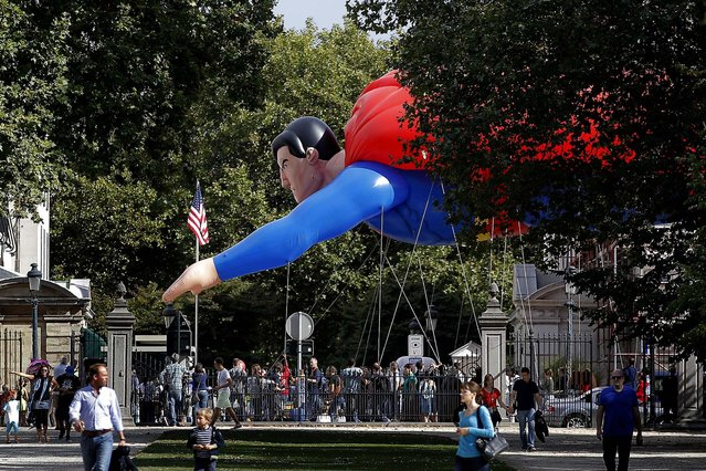 """A giant inflatable Superman flies past the U.S. embassy during the Balloon Day Parade in Brussels, on September 7, 2013. Giant figures representing well-known comic strips and Belgian characters are parading as part of the """"Comic Strip Festival"""". (Photo by Yves Logghe/Associated Press)"""