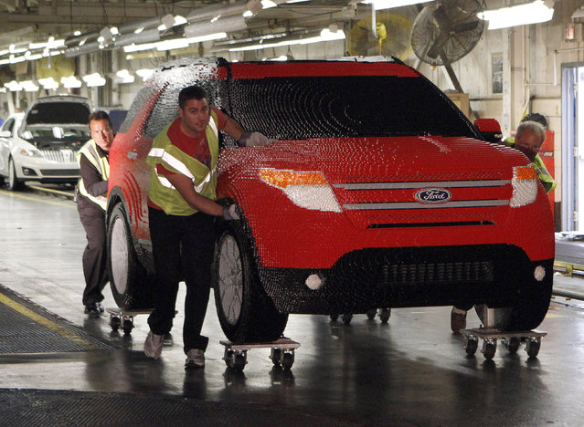 Workers from Ford's Chicago Assembly Plant push a full-size Legoland edition Ford Explorer, made with more than 380,000 Lego blocks, at Ford's Chicago Assembly Plant in Chicago, Illinois September 26, 2011. The candy-apple red Explorer will be on display at the soon-to-open Legoland Florida theme park near Orlando. (Photo by Frank Polich/Reuters)