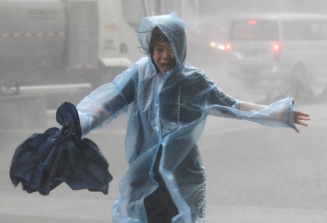 A woman runs in the rainstorm as Typhoon Mangkhut approaches, in Shenzhen, China on September 16, 2018. (Photo by Jason Lee/Reuters)