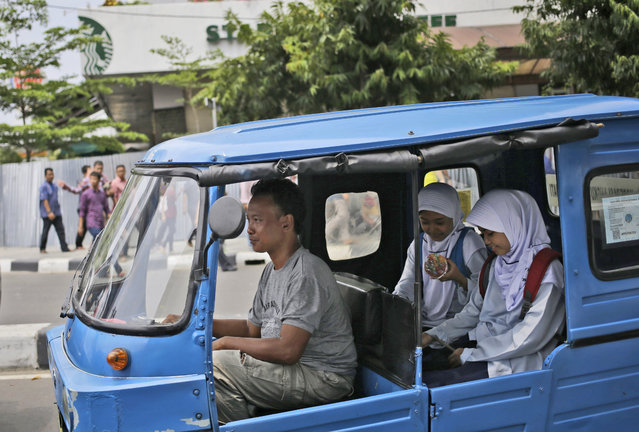 A motorized three-wheeled taxi carrying Muslim students drives past the Starbucks cafe where Thursday's attack occurred in Jakarta, Indonesia, on Friday, January 15, 2016. A day after attackers detonated bombs and engaged in gunbattles with police in the central part of Indonesia's capital, Jakarta tried to get itself back on track. (Photo by Dita Alangkara/AP Photo)