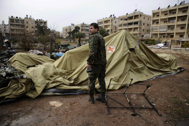 A Russian soldier checks a burned medical tent after rebels launched a mortar shell at a field hospital in west Aleppo, Syria, Monday, December 5, 2016. Rebel shelling of the government-held part of Syria's Aleppo city Monday killed a Russian female nurse in a makeshift Russian hospital in the city, a Russian officer there said. (Photo by Hassan Ammar/AP Photo)