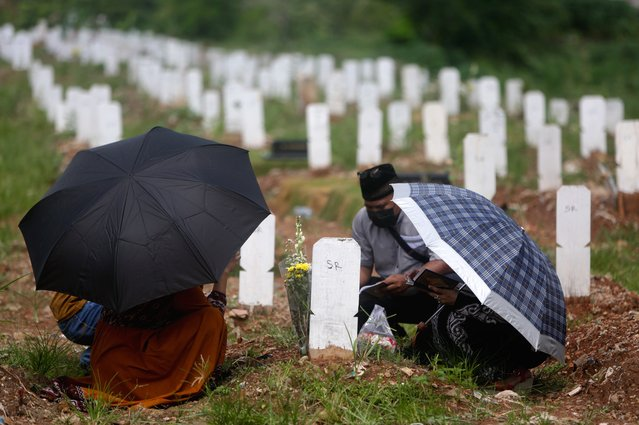 Residents pray before their relative's grave at a cemetery for victims of COVID-19 in Jakarta, Indonesia, 17 May 2021. The Jakarta government allowed residents toresume visits to the city's Public Cemetery on 17 May amid the ongoing coronavirus pandemic. (Photo by Adi Weda/EPA/EFE)