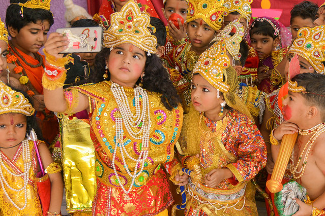 Indian children dressed up as the Hindu deities Rama and Sita take a selfie photograph at an event to celebrate the Diwali festival in Ajmer in western Rajasthan state on November 6, 2018. (Photo by Shaukat Ahmed/AFP Photo)