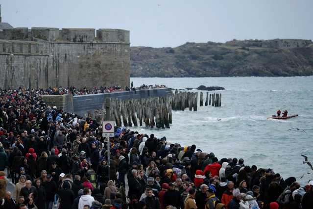 People gather on the waterfront to watch the incoming high tide in Saint Malo, western France, March 21, 2015. (Photo by Stephane Mahe/Reuters)