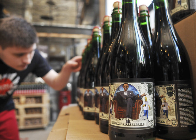 A visitor looks at bottles of stout depicting U.S. President Barack Obama, in a restaurant in Ukraine's western city of Lviv on Saturday, March 21, 2015. A local brewery released bottles in a hint that Ukraine waits for more active help from the United States to combat pro-Russian separatists in the country's east. (Photo by Pavlo Palamarchuk/AP Photo)