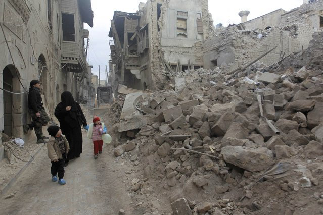 A woman walks with children as they look at a site hit by what activists say was a missile fired last night by forces loyal to Syria's President Bashar al-Assad in Aleppo's al-Bayyada neighbourhood January 2, 2015. (Photo by Jalal Al-Mamo/Reuters)