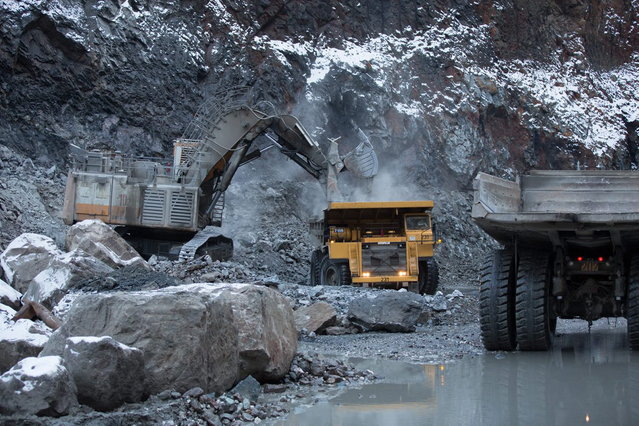 An excavator loads a dump truck with diamond ore at the base of the open pit at the Udachny diamond mine operated by OAO Alrosa in Udachny, Russia, on Sunday, November 17, 2013. (Photo by Andrey Rudakov/Bloomberg)
