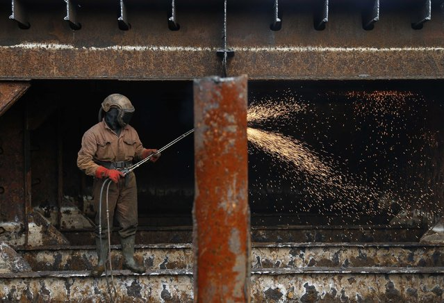 A worker uses a cutting torch to dismantle the hull of a barge at the Galloo ship recycling plant in Ghent March 24, 2015. (Photo by Francois Lenoir/Reuters)