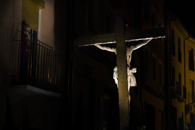 "A woman watches as penitents from ""Las Siete Palabras (Seven words)"" brotherhood carry an image of Jesus Christ during a procession in Zamora, Spain, on the early hours of Wednesday, April 1, 2015. (Photo by Andres Kudacki/AP Photo)"