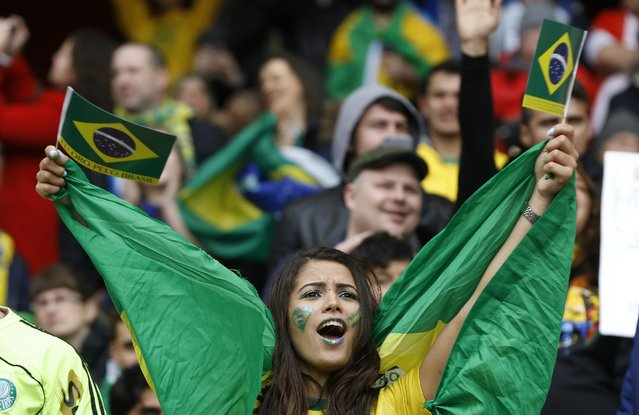 A Brazilian soccer fan waves her nations flag as she wait for the start of the international friendly soccer match soccer match between Brazil and Chile at the Emirates stadium in London, Sunday, March 29, 2015. (Photo by Kirsty Wigglesworth/AP Photo)