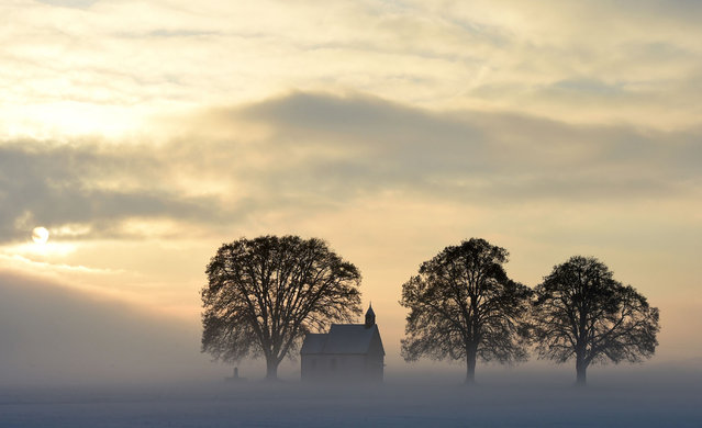 Fog surrounds a small church not far from the small Bavarian village Apfeltrach near Landsberg, southern Germany, during a cold winter morning with temperatures of minus five degrees on January 3, 2017. (Photo by Christof Stache/AFP Photo)