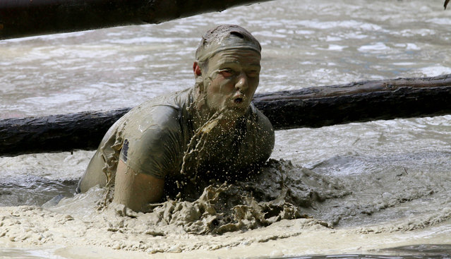 A participant of the Wild Sau Dirt Run 2015 passes a mud obstacle in Obertriesting, Lower Austria, Austria, Saturday, April 4, 2015. (Photo by Ronald Zak/AP Photo)