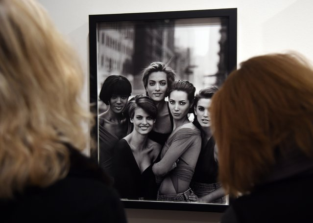 "Journalists look at a photo of famous models at the press preview for ""Vogue 100: A Century of Style"" exhibiting the photographs that has been commissioned by British Vogue since it was founded in 1916 at National Portrait Gallery on February 10, 2016 in London, England. (Photo by Stuart C. Wilson/Getty Images)"
