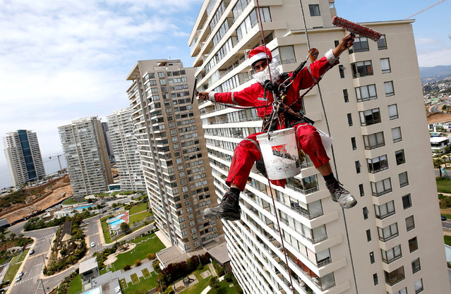 A worker waves as he cleans the windows of a building, dressed as Santa Claus, in Concon, Chile  December 22, 2018. (Photo by Rodrigo Garrido/Reuters)