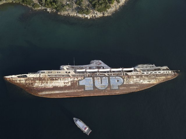 "In this Friday, December 4, 2018 photo, a half sunken cruise ship lays on its side, in the Gulf of Elefsina, west of Athens. Dozens of abandoned cargo and passenger ships lie semi-submerged or completely sunken around the Gulf of Elefsina, near Greece's major port of Piraeus. Now authorities are beginning to remove the dilapidated ships. Some of them have been there for decades, leaking hazards like oil into the environment and creating a danger to modern shipping. One expert calls the abandoned ships ""an environmental bomb"". (Photo by Thanassis Stavrakis/AP Photo)"