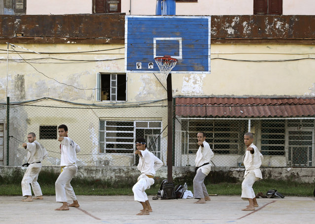 Men practice martial arts on a basketball court in Havana, Cuba, August 2010. (Photo by Desmond Boylan/Reuters)