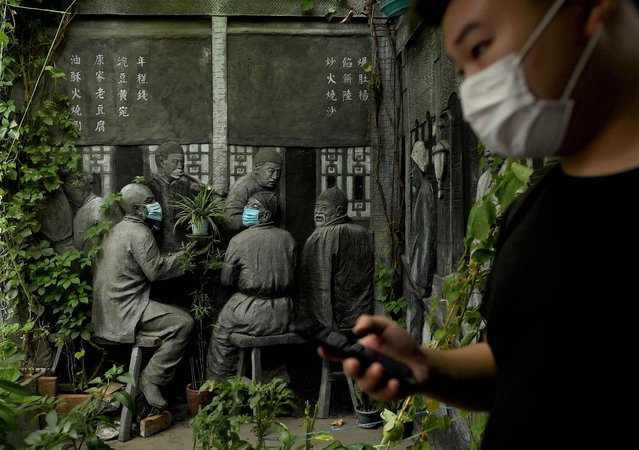 A man walks pat sculptures with face masks on along an alley in Beijing on August 3, 2021. (Photo by Noel Celis/AFP Photo)