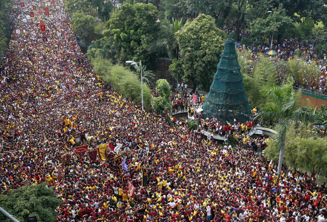 Filipino Roman Catholic devotees climb the carriage to kiss and rub with their towels the image of the Black Nazarene, lower left, during a procession to celebrate its feast day Monday, January 9, 2017 in Manila, Philippines. The raucous celebration drew tens of thousands of devotees in a barefoot procession that last for several hours around Manila streets and end up with several people injured. (Photo by Bullit Marquez/AP Photo)