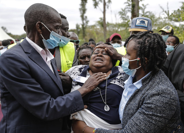 A relative cries as mourners prepare to bury coronavirus victim Nancy Ndanu Musyoka 27 years old with her daughter Jaylla Musyoka in Kakungu village, Kitui county, Kenya, Wednesday, July 28, 2021. Nancy, a high school teacher started feeling unwell and was taken to Kitui referral Hospital with breathing complications where she succumbed to covid 19 due to lack of oxygen in the hospital. According to WHO Kenya has been experiencing dengue fever outbreaks every year for the last five years. (Photo by Brian Inganga/AP Photo)