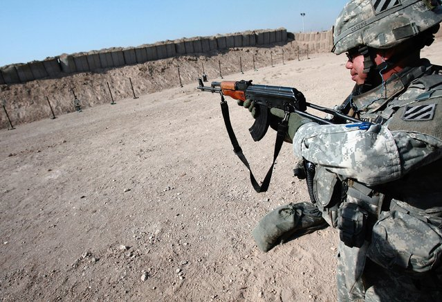 A member of the 2-69 Armored Battalion of the 3rd Infantry Division fires the AK-47 assault rifle during target practice November 24, 2007 in Baghdad, Iraq. (Photo by Chris Hondros/Getty Images)