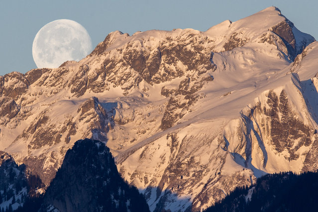 "The waning moon is setting over the mountain ""Les Cornettes de Bise"" located at the border of the Haute-Savoie and the Valais canton of Switzerland in the Chablais Alps, photographed from Glutieres, January 7, 2015. (Photo by Anthony Anex/EPA)"