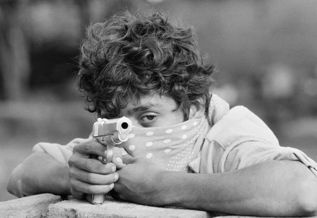 A young Sandinista guerrilla takes aim with his 45 pistol as he stands waiting to do combat with the Nicaraguan National Guard in Managua June 23, 1979. The guerrillas still occupy major parts of the Capitol City. (Photo by McLendon/AP Photo)