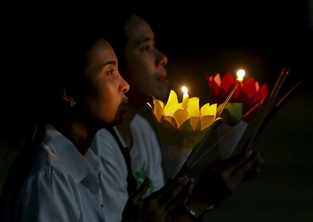 A couple pray as they carry candles during Makha Bucha Day in Nonthaburi province, on the outskirts of Bangkok, Thailand, February 22, 2016. Makha Bucha Day honours Buddha and his teachings, and falls on the full moon day of the third lunar month. (Photo by Chaiwat Subprasom/Reuters)