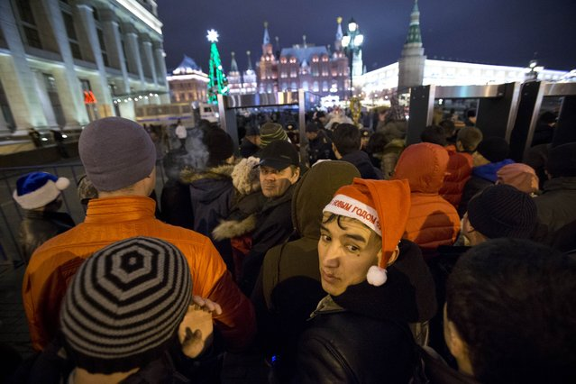People wait to be checked by police as they arriving at the Red Square ahead of the New Year's Eve festivities, in Moscow, Russia, Tuesday, December 31, 2013. (Photo by Pavel Golovkin/AP Photo)