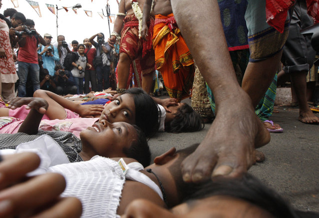 A girl watches as a Hindu holy man (not pictured) touches a child with his foot as part of a ritual to bless him during the Gajan festival in Kolkata April 13, 2015.  Hundreds of faithful devotees offer sacrifices and perform acts of devotion during the festival in the hopes of winning the favour of Hindu god Shiva and ensuring the fulfillment of their wishes, and also to mark the end of the Bengali calendar year. (Photo by Rupak De Chowdhuri/Reuters)