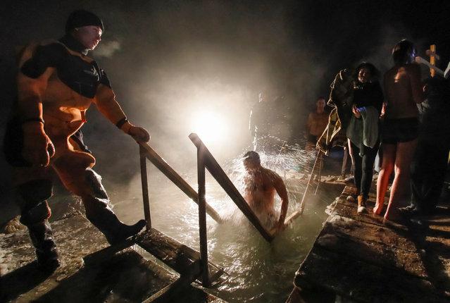 People watch as a man takes a dip during Orthodox Epiphany celebrations at the Bolshaya Almatinka river bank in Almaty, Kazakhstan, January 19, 2017. (Photo by Shamil Zhumatov/Reuters)