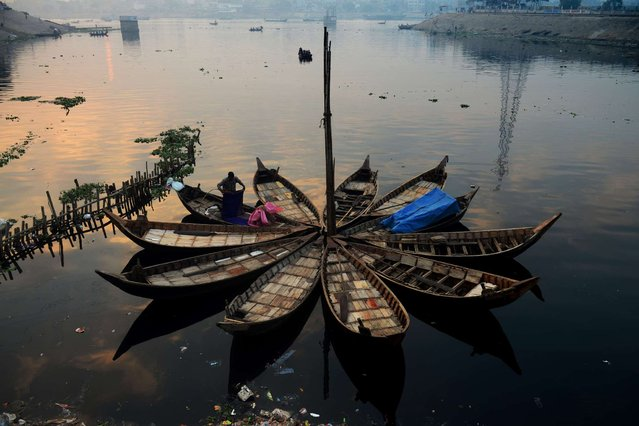 A Bangladeshi boatman tidies up his bedding after waking up in the early morning in Dhaka on January 3, 2014. Bangladesh's Prime Minister Sheikh Hasina is certain to cement her grip on power at elections scheduled for Janaury 5, boycotted by her rivals and shunned by the West after unprecedented bloodshed. (Photo by Munir Uz Zaman/AFP Photo)