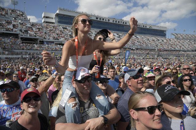 Fans watch as Jake Owen performs before a NASCAR Daytona 500 auto race at Daytona International Speedway, Sunday, February 17, 2019, in Daytona Beach, Fla. (Photo by Phelan M. Ebenhack/AP Photo)