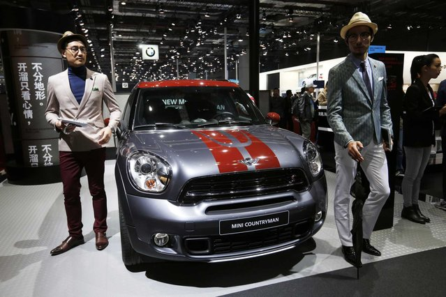 Models pose beside the Mini Cooper Countryman car on display at the 16th Shanghai International Automobile Industry Exhibition in Shanghai, China, 20 April 2015. (Photo by How Hwee Young/EPA)