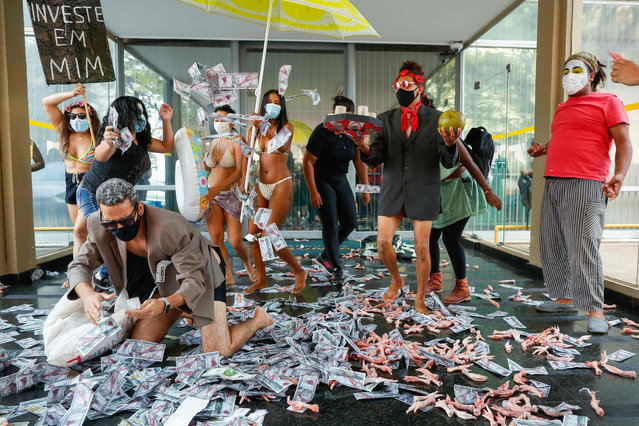 """People protest against Brazilian Economy Minister Paulo Guedes at the Economy Ministry in Brasilia on October 7, 2021, just days after he was mentioned in the """"Pandora Papers"""" media investigation exposing world leaders' use of tax havens. Guedes, mentioned in the international journalistic investigation on the concealment of assets in tax havens, assured that all his private activities were declared to the Brazilian treasury and are legal. (Photo by Sergio Lima/AFP Photo)"""