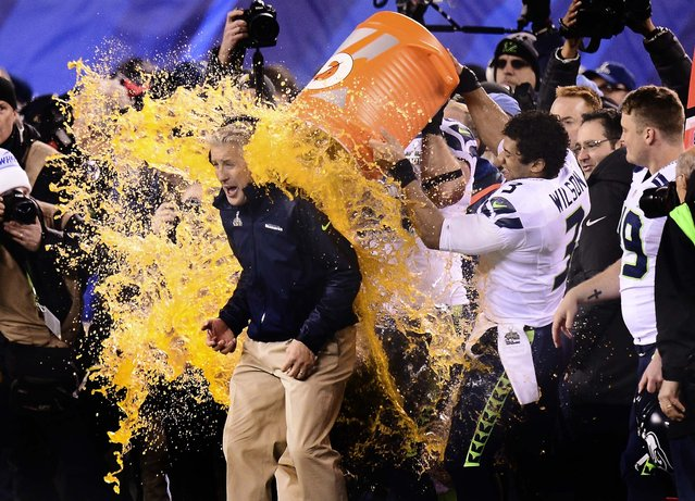 Seattle quarterback Russell Wilson and other Seahawks players bathe head coach Pete Carroll with Gatorade near the end of the game, on February 2, 2014. (Photo by Ben Solomon/The New York Times)