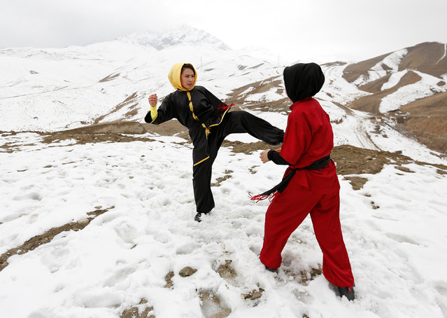 Sima Azimi (L), 20, a trainer at the Shaolin Wushu club, and Shakila Muradi, 18, show their Wushu skills to other students on a hilltop in Kabul, Afghanistan January 29, 2017. (Photo by Mohammad Ismail/Reuters)