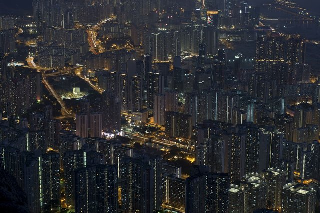 This long exposure picture shows apartment buildings and office blocks clustered together in Hong Kong's Kowloon district on February 3, 2014. Home prices in the southern Chinese city have risen by 120 percent since 2008, and by more than 30 percent from their previous peak in 1997, with prices in the luxury market being pushed up by wealthy buyers from mainland China. (Photo by Alex Ogle/AFP Photo)
