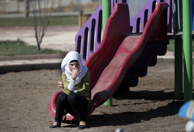 A Syrian refugee girl sits at a playground at the Oncupinar refugee camp for Syrian refugees next to the border crossing with Syria, near the town of Kilis in southeastern Turkey, Thursday, March 17, 2016. The European Union and Turkey hope to reach a comprehensive deal this week to tackle illegal migration and the refugee crisis spurred by conflicts in Syria and beyond. In return for its efforts, Turkey stands to gain $3.3 billion in EU funding to help it improve the situation of the 2.7 million Syrian refugees already within its borders. (Photo by Lefteris Pitarakis/AP Photo)