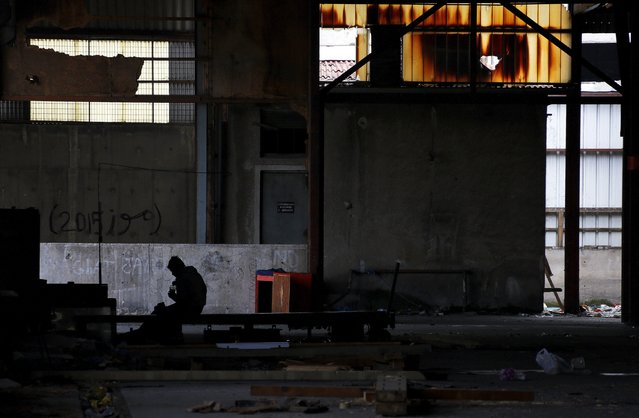 An Afghan immigrant is sits inside a wood factory across the street from a ferry terminal in the western Greek town of Patras April 28, 2015. (Photo by Yannis Behrakis/Reuters)
