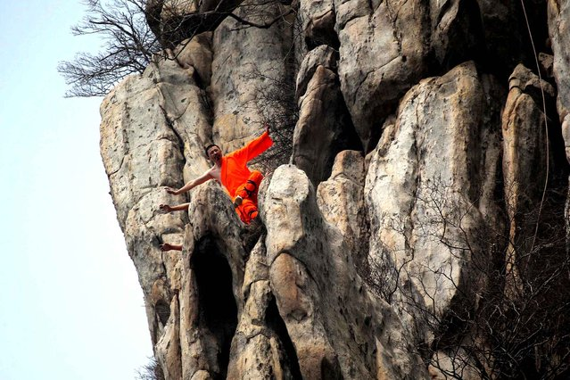 his photo taken on March 17, 2016 shows Shaolin monks practising kungfu on a cliff at the Sanhuangzhai scenic spot of Songshan mountain in Dengfeng, central China's Henan province. (Photo by AFP Photo/Stringer)