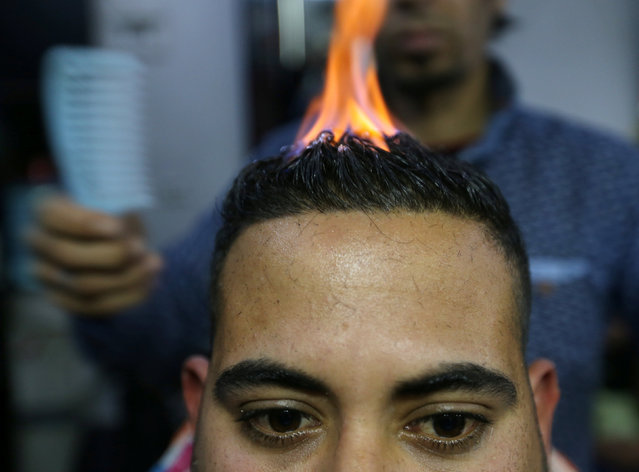 Palestinian barber Ramadan Odwan styles and straightens the hair of a customer with fire at his salon in Rafah, in the southern Gaza Strip February 2, 2017. (Photo by Ibraheem Abu Mustafa/Reuters)