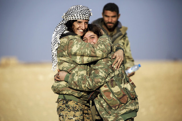 "Rougine, a 19-year-old female Arab fighter among the Syrian Democratic Forces, made up of US-backed Kurdish and Arab fighters, stands in fatigues embracing another colleague near the village of al-Torshan, 20 km on the outskirts of Raqa on February 6, 2017. Unlike Syria's Kurds, who have emphasised gender equality in both their militias and nascent autonomous governing institutions in north and northeast Syria, the Arab tribes in the same region are among the more conservative segments of the country's population, and most Arab families find the concept of female fighters ""hard to accept"". (Photo by Delil Souleiman/AFP Photo)"