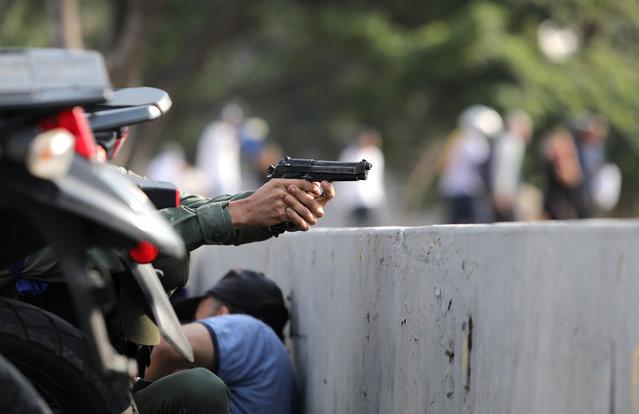 "A military member aims a gun near the Generalisimo Francisco de Miranda Airbase ""La Carlota"", in Caracas, Venezuela April 30, 2019. (Photo by Manaure Quintero/Reuters)"