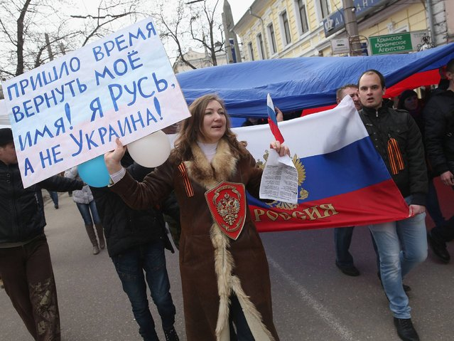 "Pro-Russian protesters, including one woman holding a sign that reads: ""The time has come to return my name! I am Russia. And not Ukraine!"", hold up a giant Russian flag as they march in Simferopol, Ukraine, on 1 March. (Photo by Sean Gallup/Getty Images)"