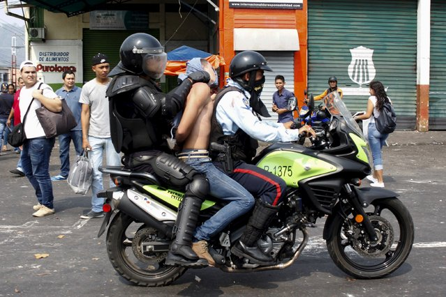 Police officers detain a demonstrator (C) on a motorcycle during a protest against the increase in the price of public transport in San Cristobal March 29, 2016. (Photo by Carlos Eduardo Ramirez/Reuters)