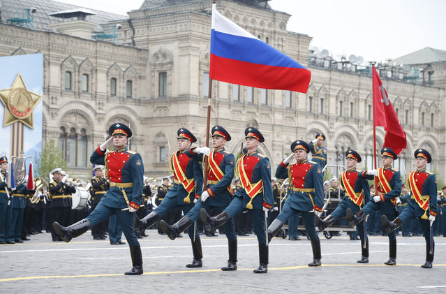 Russian honour guard carry a national flag, left, and a replica of the Victory banner during the military parade to celebrate 74 years since the victory in WWII in Red Square in Moscow, Russia, Thursday, May 9, 2019. (Photo by Alexander Zemlianichenko/AP Photo)