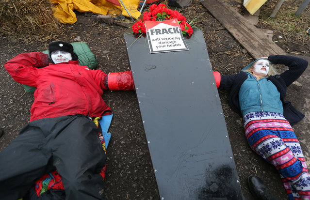 """Two unnamed anti-fracking protesters lie in the road after engaging in a """"lock-on"""" near the Barton Moss exploration facility on March 6, 2014 in Barton, England. Campaigners, who have been on the site in Barton Moss Road since November last year, are awaiting a court decision today as to whether they are to be lawfully evicted. (Photo by Dave Thompson/Getty Images)"""